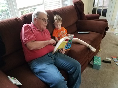 Grandpop reads about the Justice League to Samson
