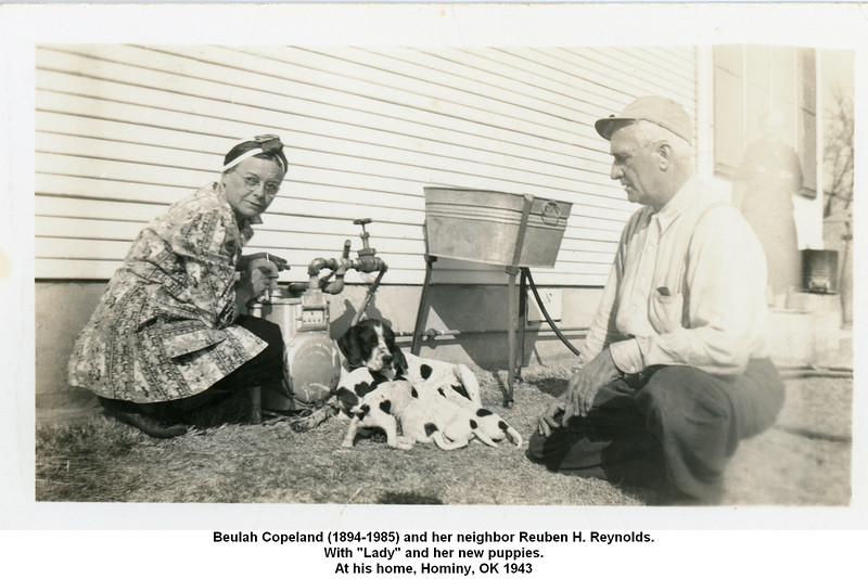 "Beulah Copeland (1894-1985) and her neighbor Reuben H. Reynolds.<br /> With ""Lady"" and her new puppies.<br /> At his home, Hominy, OK 1943"