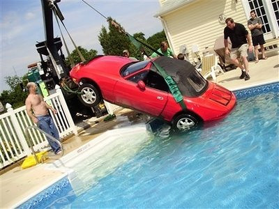 This photo released by Ashley Campasino  shows a red Mazda Miata being pulled out from the bottom of the Campasino family swimming pool in Stewartstown, Pa. on June 30, 2008. Kim Taylor thought she had set the emergency brake. But her wayward red convertible nonetheless rolled downhill, crashed through a fence and plunged into her neighbors' in-ground pool. (AP Photo/Courtesy Ashley Campasino)  ** NO SALES **