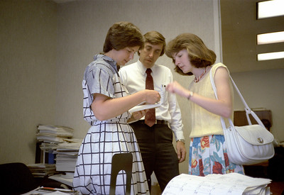 Sharon McMahon, Vic Brungart, and Kathleen Feeney examining some photos.  June 1986.