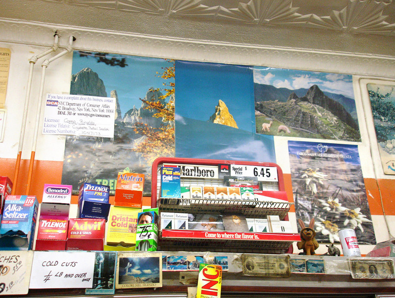 The walls are decorated with posters from various places in Italy.  Above the beer can Edelweiss is seen.