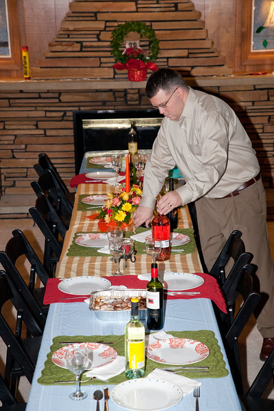 Thanksgiving table, pre-dinner.  Ian is placing the wine bottles on the table.