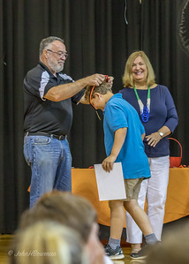 4th Grade Awards: Henry Receives Honor Roll Medal from Mr. Greene