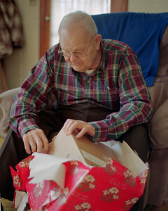Noval Cantrel un wraping his Christmas present at Veda's in Mountain View, Missouri. 1993
