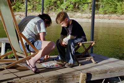 Lela and Bobby play a board game on the boat dock; Lake of the Ozarks. October, 2000.