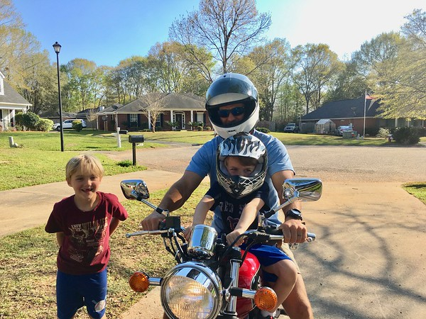 Luca getting a ride on Uncle Craig's motorcycle with cousin Cedar looking on.