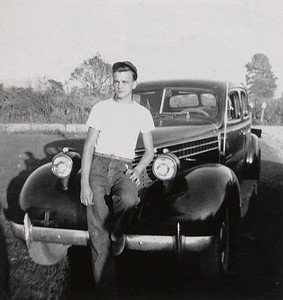 George Junior Wright standing in front of an automobile. About 1950.