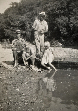 Elmer Clark, George Junior, George William, and Dorothea Wright in a john boat on a river bank.