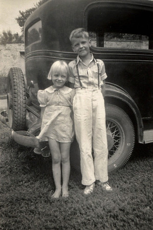Dorothea and George Junior, standing in front of an old car. About 1939.