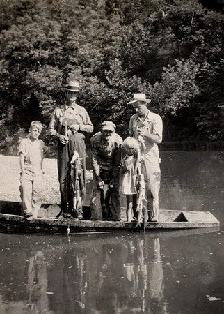 George Junior, Elmer Clark, Oliver Lemons, Dorothea and George William Wright in a john boat on a river bank.