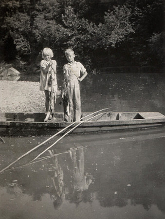 Dorothea and George Junior Wright in a john boat on a river bank.