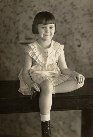 Norma Davenport, as a child, seated on a bench.