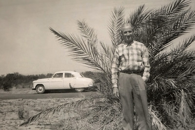 Roscoe Davenport standing in front of a palm shrub and a car. Probably California or possibly Arizona