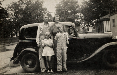 George and Gladys Wright, Dorothea and George Junior, standing in front of an old car.
