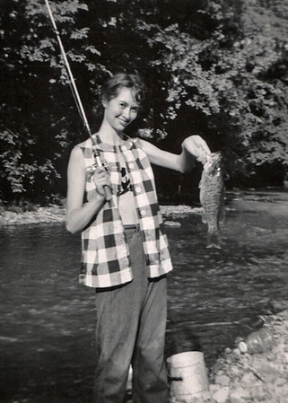 Norma, holding a freshly caught fish. Written on the phoro: Her biggest yet! Opening Day '51