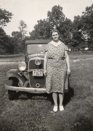 Gladys Wright standing in front of an old car. Date on license plate is 1941.