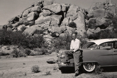 Roscoe Davenport sitting on his car in the desert. Car appears to be a Pontiac, from about 1956.