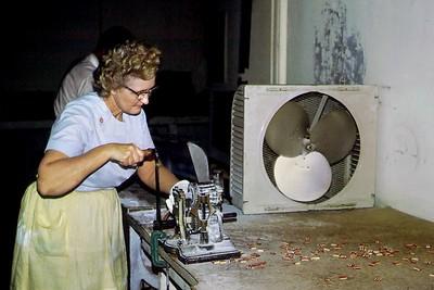 Chloe Mae Cunningham turning the hand crank to make sassafrass drops. Cunningham Candy Company, Springfield, Missouri. 1971.