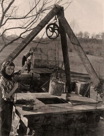 Cara drawing a bucket of water from the well on Hazel's place near West Fork, Arkansas. 1962 Scan is from a Polaroid print made by George Wright.