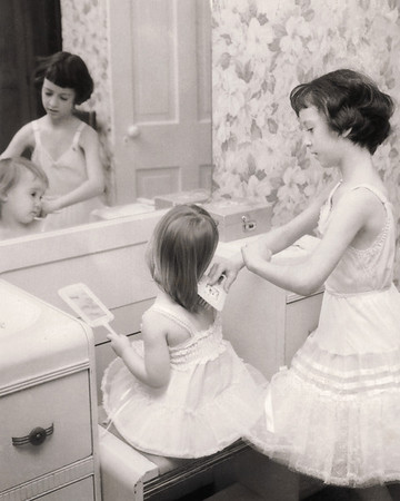 Cara brushing Lisa's hair in front of Mom's mirror.  Scan is from a Polaroid print made by George Wright.1960