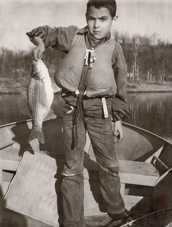 Gary standing in a lake boat holding a fish. Scan is from a Polaroid print made by George Wright.