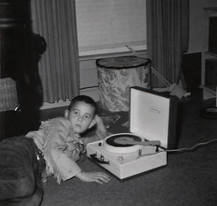 Gary Wright in fringed shirt listening to a phonograph in February, 1959.