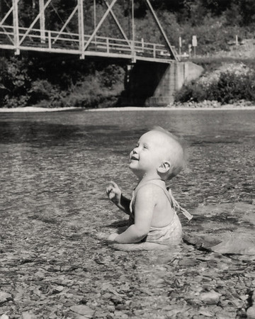 Lisa, sitting in Swan Creek near Garrison, Missouri. 1959 Scan is from a Polaroid print made by George Wright.