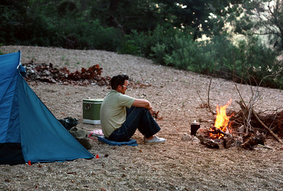 George Wright sitting by a campfire on a gravel bar. Overnight canoe trip, 1975.
