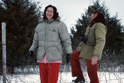 Norma and George Wright climb a wire fence. Fellows Lake, Winter, about 1979.