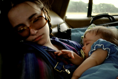 Lisa and Baby Olivia sleeping in the back seat of a car. 1979.