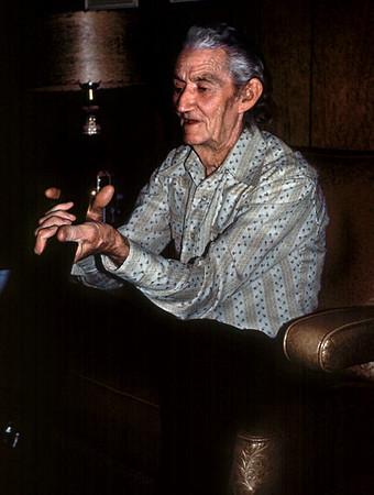 Roscoe Davenport examines a gun at his and Hazel's house. 1976.