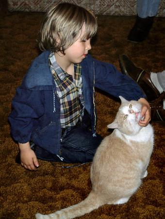 Sean Melton petting a cat. Norma's, 1978.