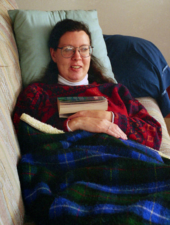 Rita relaxes with a book in her living room, 1996.