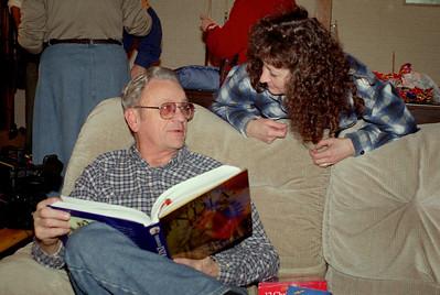 George and Cara look at a book. Christmas at Cara's, 1997.