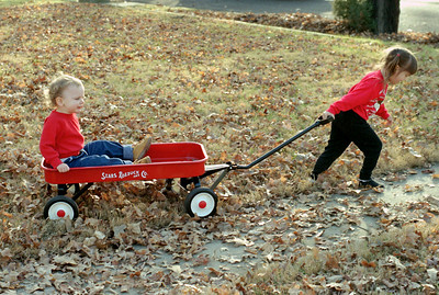 Kelsey pulls Jake in a red wagon; Christmas at Normas, 1993.