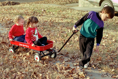 Jared pulls Kelsey and Jake in a red wagon; Christmas at Normas, 1993.