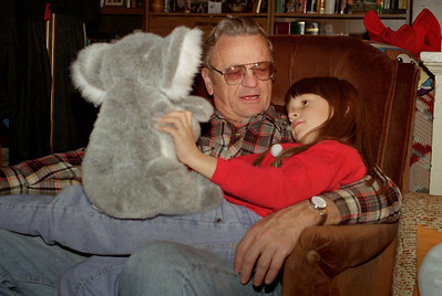 Kelsey with her stuffed toy in George's lap. Christmas at Normas, 1996.