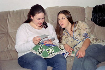 Sisters Olivia and Jessica look at photos; Thanksgiving at Cara's, 2002.