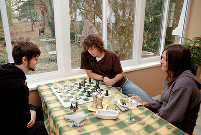 Jared and Jake play chess, while Kelsey eats olives; Thanksgiving dinner at Rita's. November, 2007.