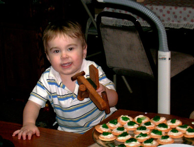 Simon plays with a toy while eyeing the cookies. Christmas at Norma's, 2006. (File name is incorrect.)