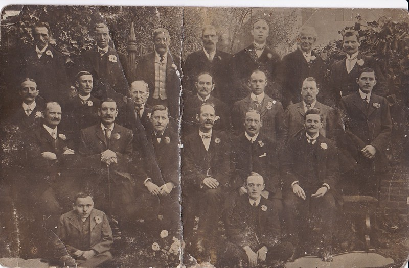 Sidney Godwin Hendy sitting on the ground (right) with his father, Thomas Godwin Hendy third from the left on the center row.