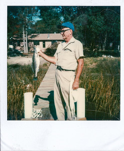 Grandpa Smith on his small dock  (before he put in a boat house). The tall double pines were the ones that were hit by lightning while we were there.