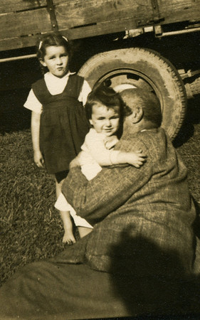 My grandfather Frank Bray holding me, my cousin Beverley Duguid looking on.  This was taken at my Grandfather's property 'Kynnumboon' at Murwillumbah, New South Wales - probably around 1952 - I'm guessing that is my mother's shadow on Grandpa's hip.
