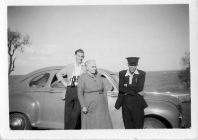 Aggie sent this photo to my Grandmother - she wrote on the back  Frank Roser - on the right - he lives with us and owns the car.  Myself (Agness Tolson (nee Maddock) & the baby I adopted 20 years ago (standing behind Aggie)- Malcolm David - 6ft 1 1/2ins and weighs over 13 stone,  Aggie Hepple (nee Tolson) took the snap last August on Moffatts Heads, Caloundra.  Photo from my Grandmother's Collection - May McGilvery