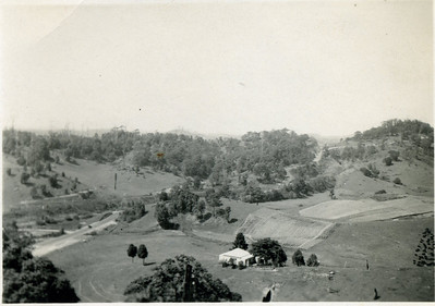 Looking down on Grandma's house at Crabbes Creek in northern New South Wales. The old Pacific Highway winds its way down the hill.  Stamped on back - Wards Studio, Mullumbimby. Inscription on back reads - 'This place showing road & railway'  Photo from my grandmother's collection - May McGilvery (nee Munro)