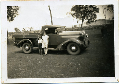 Peter & Betty English  Nell has written on the back of the photo - 'The two kids were well in them all, you can see one of the head lights of the truck tied up, we haven't got it fixed yet, a fellow backed into it & broke it in Bell one day.  Photo from my grandmother's collection - May McGilvery (nee Munro)