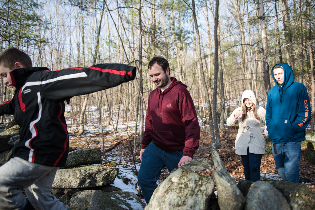 . (01/21/18 PRINCETON MA) Sentinel & Enterprise reporter Nick Mallard steps over a stone wall as the tour at the Wachusett Meadow Wildlife Sanctuary in Princeton comes to a close on Sunday.  SENTINEL & ENTERPRISE JEFF PORTER