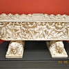 "Sarcophagus with Scenes of Bacchus; Unknown artist, Roman, Rome, A.D. 210 - 220.; with supports: 1800s Marble<br /> The inscription on the lid of this sarcophagus identifies its former occupant, Maconiana Severiana, as being from a senatorial family. ""To the soul of the deceased. For Maconiana Severiana, the sweetest daughter, Marcus Sempronius Faustinianus, vir clarissimus [holding a senatorial rank], and Praecilia Severiana, clarissima femina [from a senatorial family], her parents [had this made]."" Given the small size of the sarcophagus, Maconiana must have been a child or adolescent.<br /> <br /> The front of the sarcophagus shows a Dionysiac revel, culminating in the discovery of the sleeping Ariadne, shown lying down on the right. Abandoned by the Greek hero Theseus, Ariadne awakened to a new life with Dionysos, the god of wine. The goat-legged Pan lifts the veil from her prone figure while satyrs, maenads, and a panther surround the drunken Dionysos.<br /> <br /> The back of the sarcophagus shows another Dionysiac scene of winemaking carved in a simpler, flatter style. Panels with related figures flanking the central inscription on the lid. For the Romans, Dionysos was associated with the hope of a better afterlife; thus many sarcophagi show the god and his followers.<br /> <br /> Sculpted stone sarcophagi, which came into use in the 200s A.D., soon became symbols of wealth and status. Since Romans favored certain themes for sarcophagi, they were often bought ready-made and then customized by the addition of a portrait of the deceased. The blank face of Ariadne should have been carved as a portrait of Maconiana Severiana. Why it was left blank in this instance is not clear."
