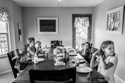 Six children, siblings, sitting at the dining room table waiting for their breakfast.