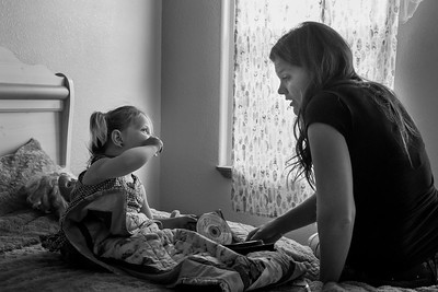 A mom helps her daughter choose a cd as she gets ready to take a nap.